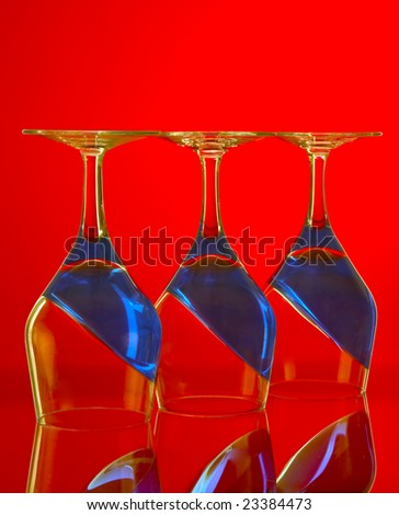 Close up of three upside down wine glasses with sloping blue contents set against a bright red background.