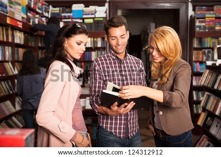 close-up of three young good looking people in a bookstore turning one page of a book and reading - stock photo