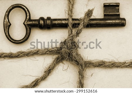 Close up of tied with twine bundle of old paper with old rusty weathered metal door keys, sepia - stock photo