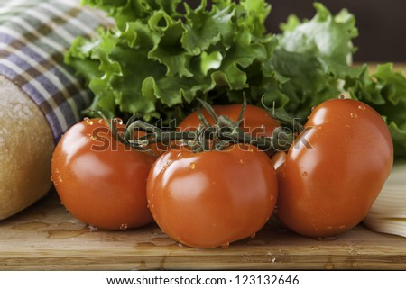 close up of tomato with loaf of rustic bread, lettuce and cheese - stock photo