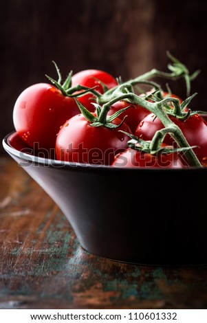 Close up of tomatoes on the vine in a bowl - stock photo