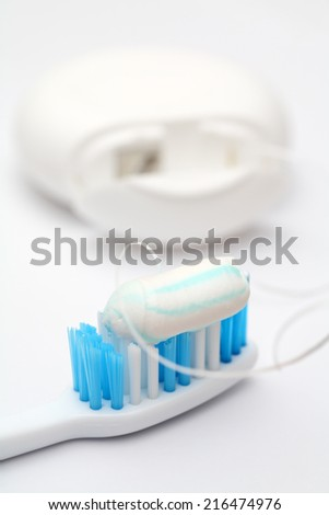 Close-up of toothbrush with toothpaste and dental floss.