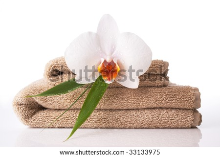 Close up of towel and orchid on reflective white surface - stock photo