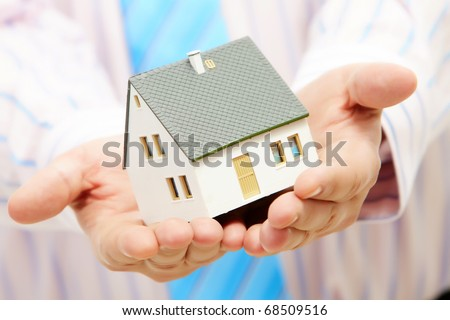 Close-up of toy house model in male hands - stock photo
