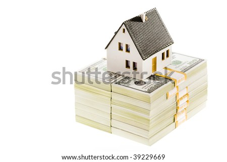 Close-up of toy house model on top of dollar stack