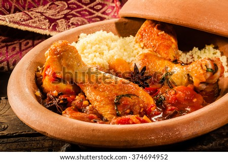 Close Up of Traditional Tajine Berber Dish Made with Chicken Legs, Couscous and Savory Tomato Sauce Served in Covered Clay Pottery Dish on Rustic Wooden Table with Napkin - stock photo