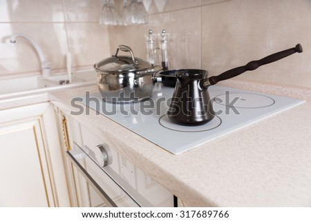 Close Up of Traditional Turkish Coffee Pot on Stove Top in Kitchen with Pots and Pans - stock photo