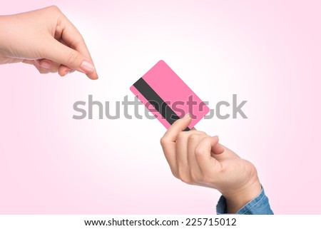 Close-up of transfer of credit card from male hand to that of female over pink background  - stock photo