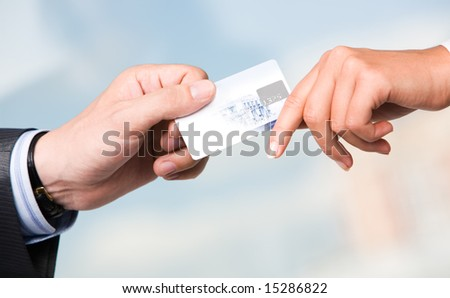 Close-up of transfer of credit card from maleâ??s hand to that of female over blue background - stock photo