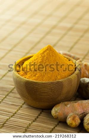 Close up of turmeric powder on bamboo mat - stock photo