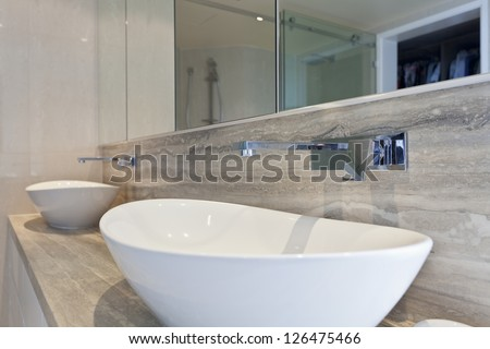 Close up of twin sinks in modern bathroom - stock photo