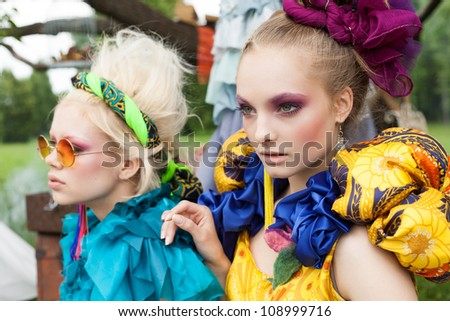 Close-up of two beautiful ladies in a garden. Outdoors - stock photo