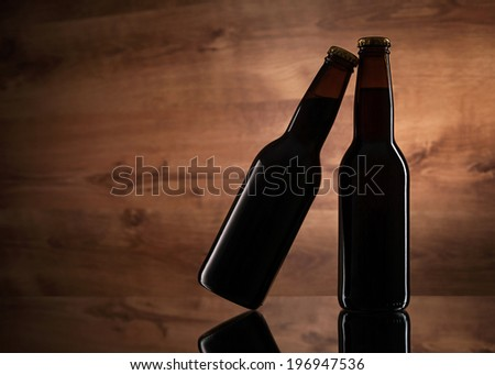 Close up of two beer bottles on wooden texture - stock photo