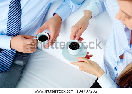 Close-up of two business partners holding cups of coffee - stock photo