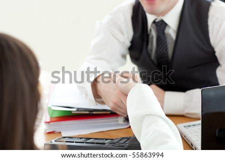 Close-up of two business partners shaking hands in the office - stock photo