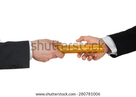 Close-up Of Two Businessman's Hand Passing A Golden Relay Baton Over White Background