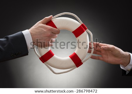 Close-up Of Two Businessman's Hand Passing Lifebuoy - stock photo