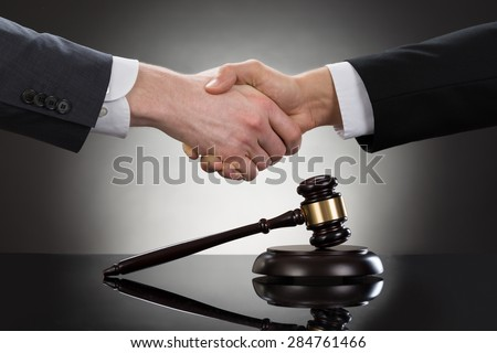Close-up Of Two Businessman Shaking Hands In Front Of Mallet - stock photo