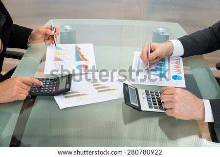 Close-up Of Two Businessmen Analyzing The Graph Using Calculator On Office Desk - stock photo