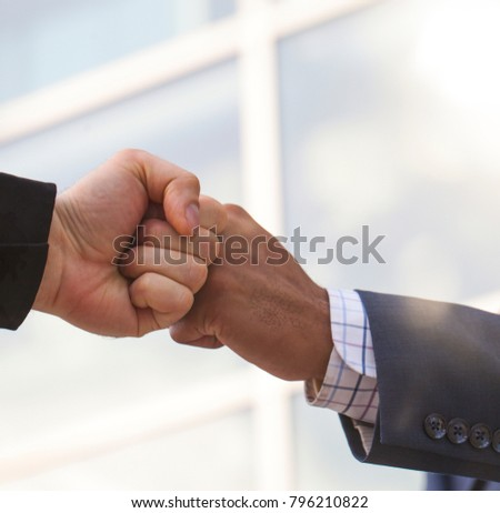 Close-up of two businessmen giving fist bump. Partnership concept