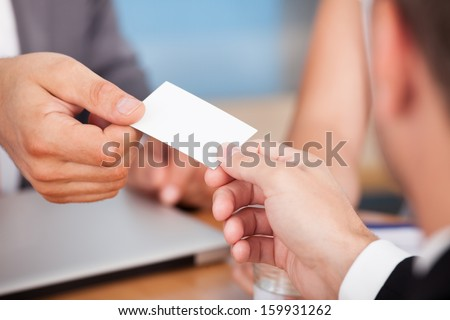 Close-up Of Two Businessmen Holding Card Over Desk - stock photo