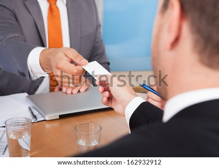 Close-up Of Two Businessmen Holding Card Over Desk