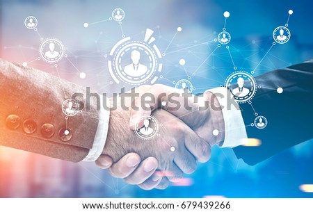 Close up of two businessmen in suits shaking hands standing against a city panorama. There is a network sketch in the foreground. Toned image double exposure mock up