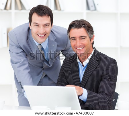 Close-up of two businessmen working at a computer in the office