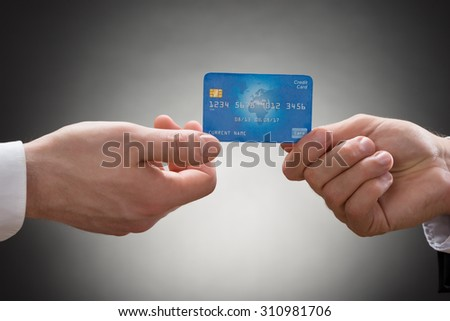Close-up Of Two Businesspeople Hands Holding Credit Card - stock photo