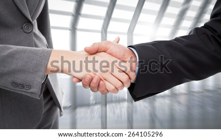 Close up of two businesspeople shaking their hands against room with large window looking on city - stock photo