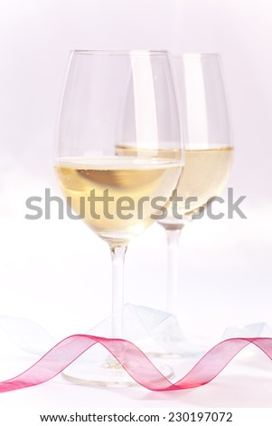 Close up of two champagne glasses surrounded by Christmas decoration