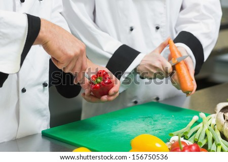 Close up of two chefs cutting vegetables in commercial kitchen