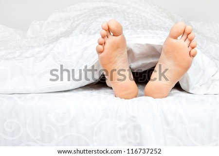 Close up of two feet in a bed
