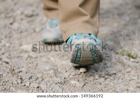 Close up of two feet with shoes are hiking on a stony way - stock photo