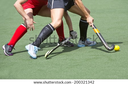 Close up of two field hockey players, challenging eachother for the control and posession of the ball during an intense, competitive match on professional level - stock photo