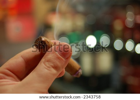 Close up of two fingers holding a cigar with blurred background - stock photo