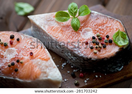 Close-up of two fresh salmon steaks with sea salt, pepper and basil leaves - stock photo