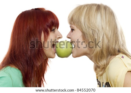 Close-up of two girls biting a green apple from another sides - stock photo