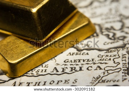 Close-up of two gold ingots on top of an old map of Africa - stock photo