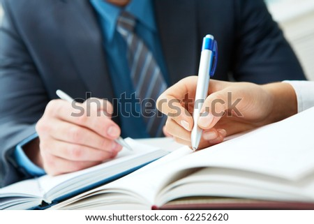 Close-up of two hands writing in notebooks - stock photo