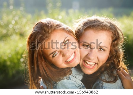 close-up of two happy teenage girls outdoors in jeans wear smiling hugging looking at camera