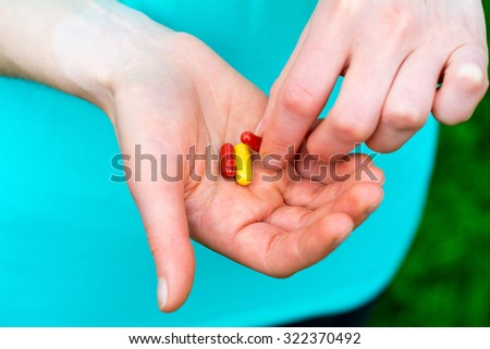 Close-up of two human hands, in the hands are capsules  - stock photo
