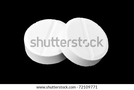 Close-up of two medicine tablets. Isolated on black