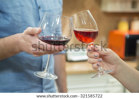 Close up of two people holding wineglasses and celebrating while toasting with red wine.
