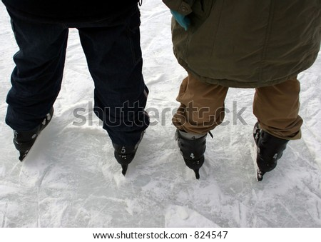 Close-up of two people ice skating together - stock photo