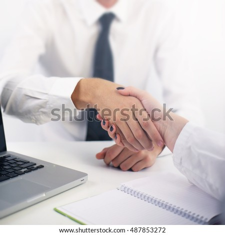 Close-up of two people shaking hands in the office