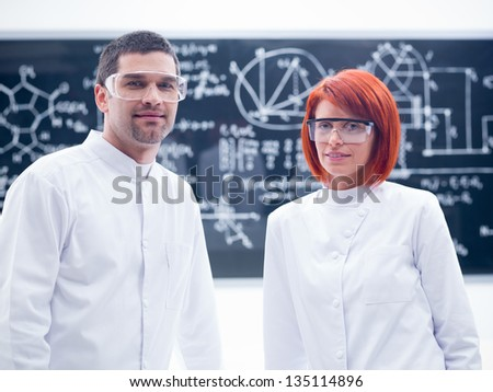 close-up of two researchers smiling  in a chemistry lab with a blackboard on the background - stock photo