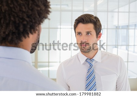 Close-up of two serious businessmen looking at each other in the office