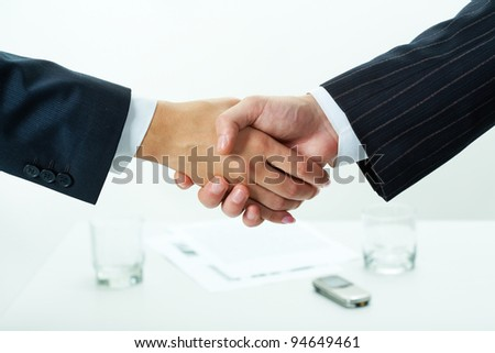 Close-up of two shaking hands over workplace with business documents on it - stock photo
