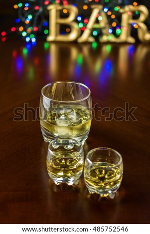 Close up of two small glasses of whiskey and glass of whiskey with ice on a bar table. Selective focus.